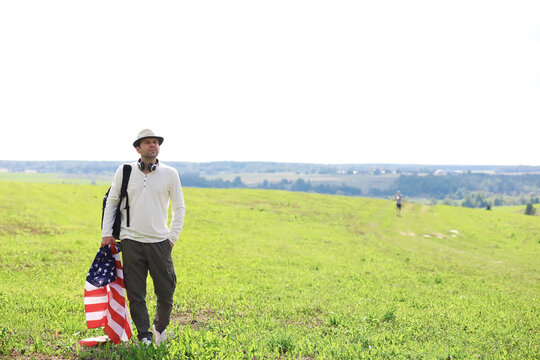 Man waving American flag standing in grass farm agricultural field , holidays, patriotism, pride, freedom, political parties, immigrant