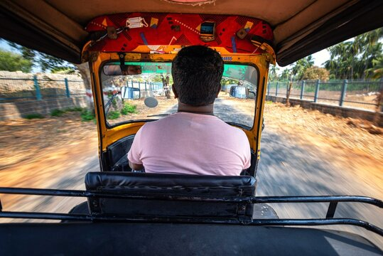 Hampi. India. Cab driver is driving a rickshaw taxi with passengers through the Indian village