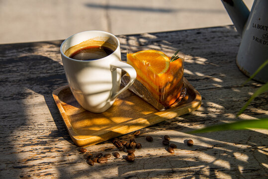 A cup of coffee with orange cake on the wooden table