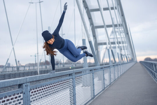 Young happy fitness woman in winter blue sportswear skips over bridge fence during cold winter day