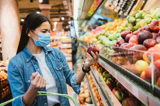 Young woman wearing face mask to stop virus spread choosing food
