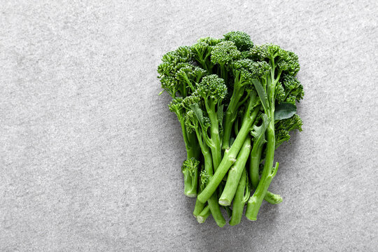 Broccolini. Fresh bunch of broccoli sprouts on a cooking table. Healthy food concept. Top down view