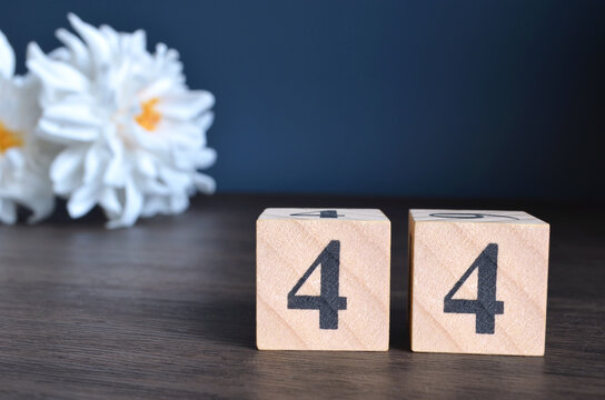 Number 44, rating, award, Empty cover design in natural concept with a number cube and peony flower on wooden table for a background.