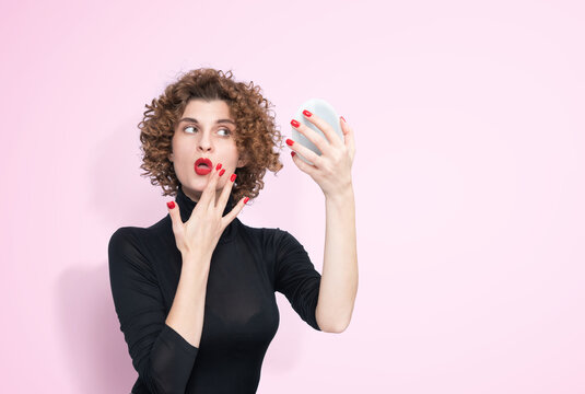 Young pretty girl in a black turtleneck looks in a small mirror and tweaks lipstick on her lips. On light pink background.