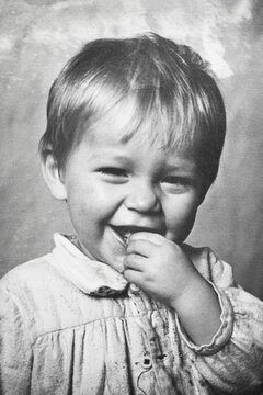 Portrait of little soviet boy holding hand near his mouth, black and white. 1950s. Old surface with artifacts, soft focus. Transferred property, family archive.