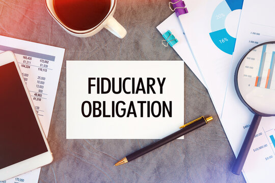 Fiduciary Obligation is written in a document on the office desk, coffee, diagram and smartfon
