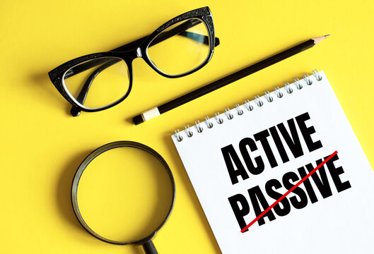 New PASSIVE - ACTIVE text written on a notebook with glasses, magnifying glass and pencil.