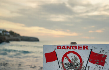 Danger, no swimming sign with red flags, blurred sea background with cliff shore, morning overcast sky above Fotobehang