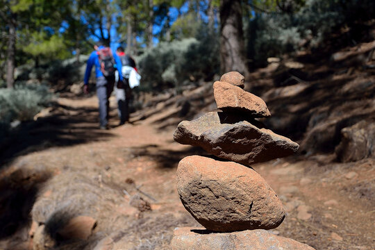 Gran Canaria, Spain -March 23, 2020: Hikers climbing a path where you can see a mark of stones