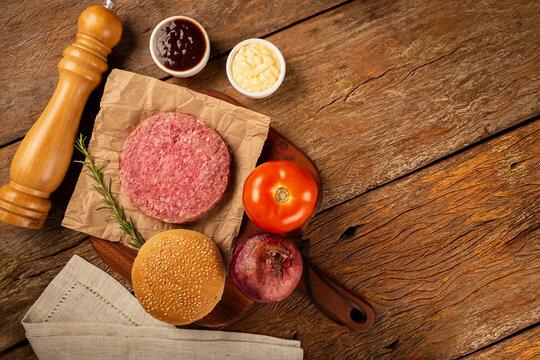 Table with ingredients for hamburger. Raw hamburger.