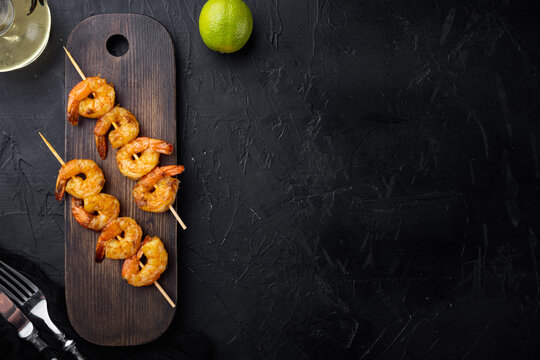 Shrimps skewers, on wooden serving board, on black background, top view flat lay , with copyspace  and space for text