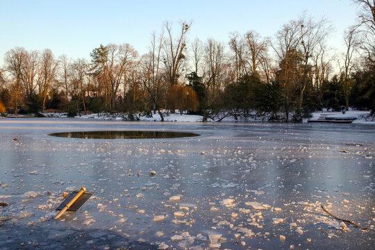 umgeknicktes schild und großes loch im zugefrorenen see