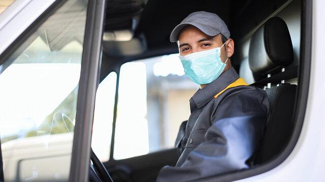 Smiling deliverer man driving a van, covid concept