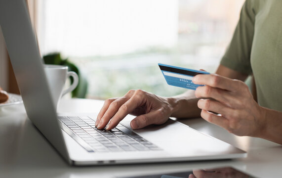 Woman using laptop computer with credit card making online payment. Business, online shopping, e-commerce, internet banking, spending money, working from home concept