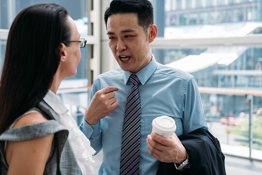 Businessman explaining something to a businesswoman and holding cup of coffee. Close up photo of handsome business man talking with female coworker in office with big windows