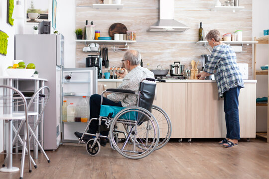 Handicapped man in wheelchair opening refrigerator and helping wife preparing breakfast in kitchen. Senior woman cooking for paralized husband, living with disabled man with walking disabilities