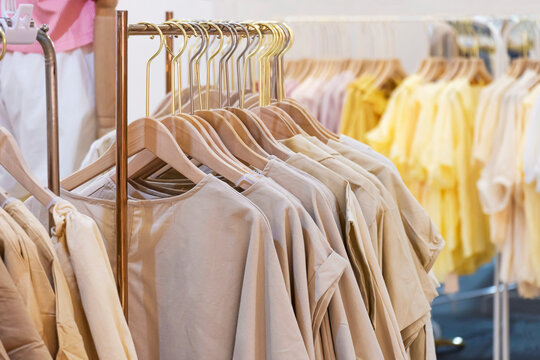 Close up image of female cotton clothes in neutral colors tone hanging on clothing rack for sale in boutique fashion store at shopping mall