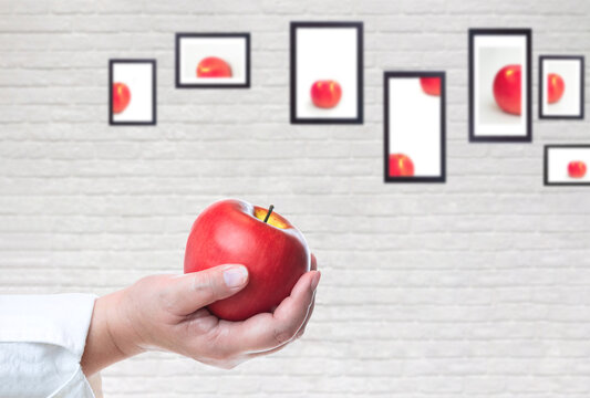Close up of healthy woman hand holding fresh red apple with blurred apple piece images in picture frames on white brick wall background, create idea for healthy food concept