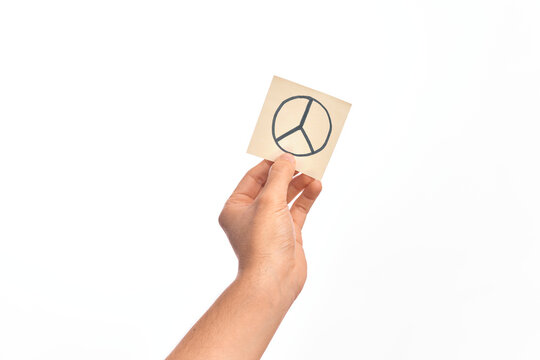 Hand of caucasian young man holding reminder paper with peace symbol over isolated white background