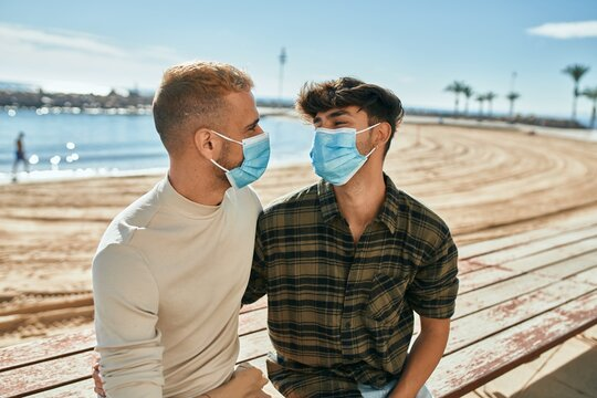 Young gay couple wearing medical mask sitting on the bench at the beach.