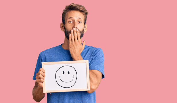 Handsome blond man with beard holding blackboard with happy face covering mouth with hand, shocked and afraid for mistake. surprised expression
