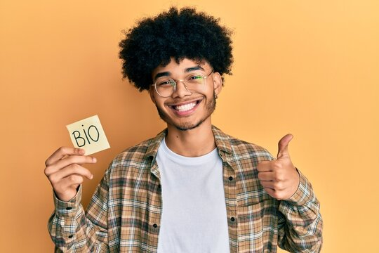 Young african american man with afro hair holding paper with bio word smiling happy and positive, thumb up doing excellent and approval sign