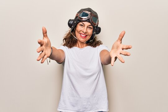 Middle age brunette woman wearing goggles and retro aviator leather hat over white background looking at the camera smiling with open arms for hug. Cheerful expression embracing happiness.