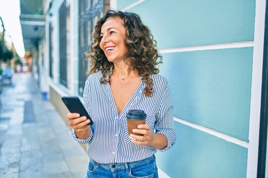Middle age hispanic woman using smartphone and drinking take away coffee at the city.