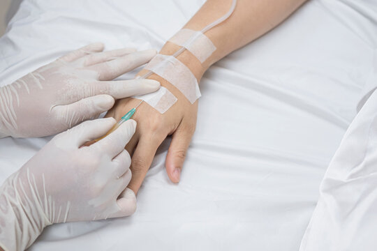 High angle view of doctor's hand injects saline infusion needle into female patient on hospital bed
