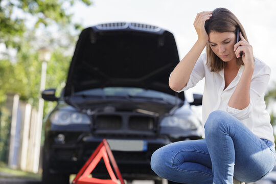 pretty woman having problem with car on the road