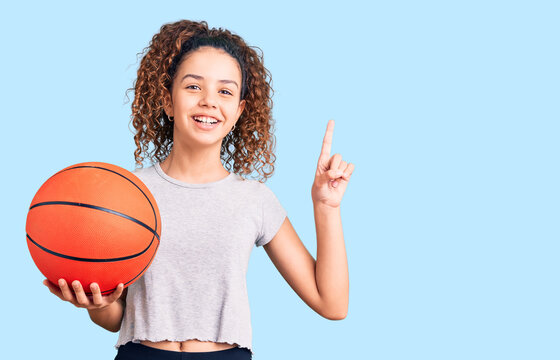 Beautiful kid girl with curly hair holding basketball ball surprised with an idea or question pointing finger with happy face, number one
