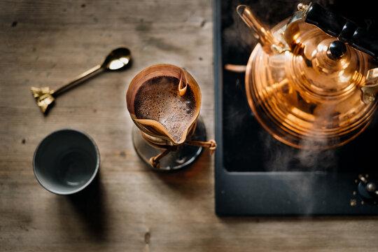 dampfender Wasserkessel und Aufbrühen von Kaffee mit der Hand