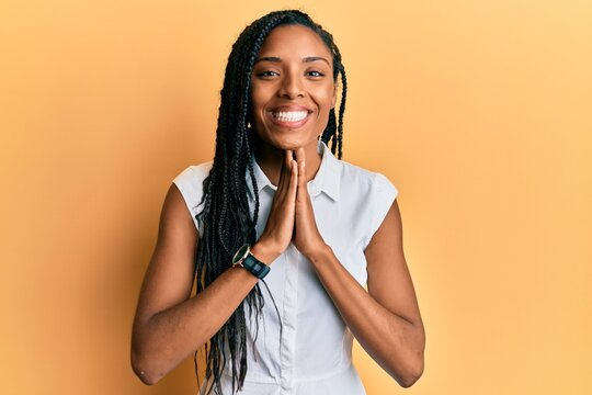 African american woman wearing casual clothes praying with hands together asking for forgiveness smiling confident.