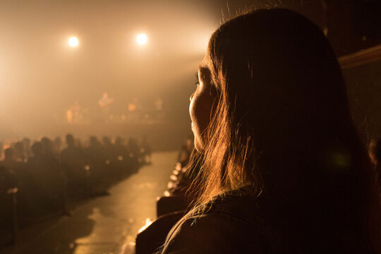 Closeup shot of a female in the hall with an audience under the lights