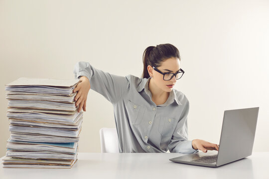 Young accountant working on laptop computer sitting at desk with pile of papers. Paperwork vs electronic documents. Storing files in digital database. Having quick convenient access to storage system