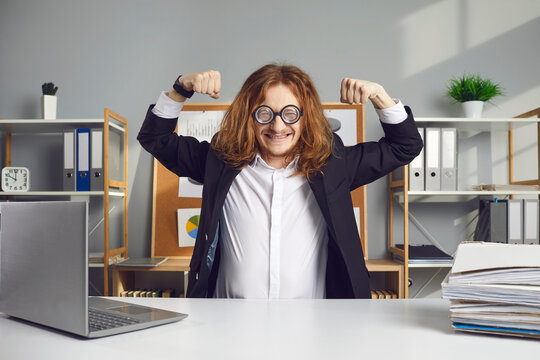Happy office worker in eyeglasses smiling and showing motivation for work. Funny man in suit sitting at desk and flexing arm muscles. Cheerful employee feeling energetic and ready for productive day