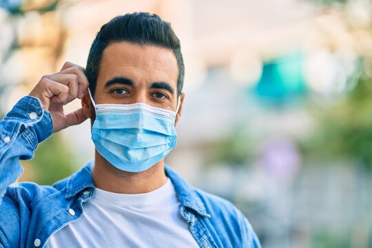 Young hispanic man putting on medical mask standing at the city.