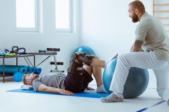 Teenage girl after car accident with orthosis on the leg exercises on blue mat in the company of physiotherapist