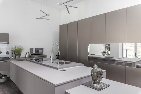 Grey modern kitchen with island and silver accessories
