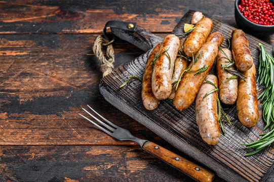 Grilling bavarian sausages on a cutting board. Dark wooden background. Top view. Copy space