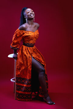 beautiful elegant african woman in traditional dress on red background, studio shot