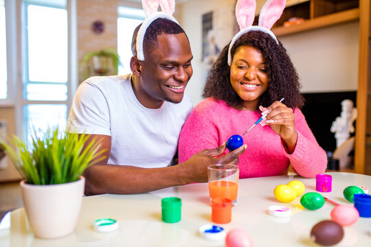 Young african american man and woman wearing cute easter bunny ears and painting eggs in the house
