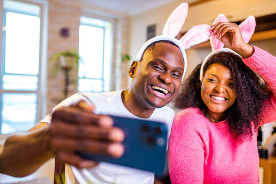 Young african american man and woman wearing cute easter bunny ears in the house taking selfie on smartphone