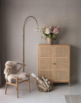 Skandinavische Inneneinrichtung mit Schrank, Stuhl, Wandlampe und einer Vaser voller Pfingstrosen