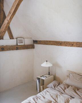 Schlafzimmer mit Bett und Beistilltisch und Lampe in einem Landhaus mit Holzbalken