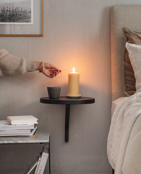 Frau zündet Kerze im Schlafzimmer an