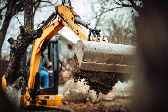 Worker using excavator and bulldozer for landscaping works