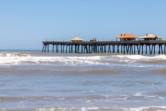 Fishermen pier, sand and waves