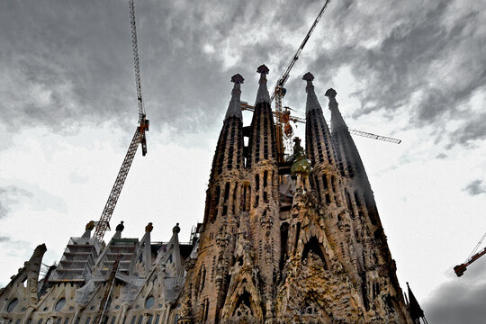 Storm clouds gather above The Nativity Facade.  View up at multilevel Tower Cranes working on additional towers designed by Catalan architect Antoni Gaudí