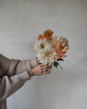 Frau hält Blumenstrauß aus Dahlien in der Hand